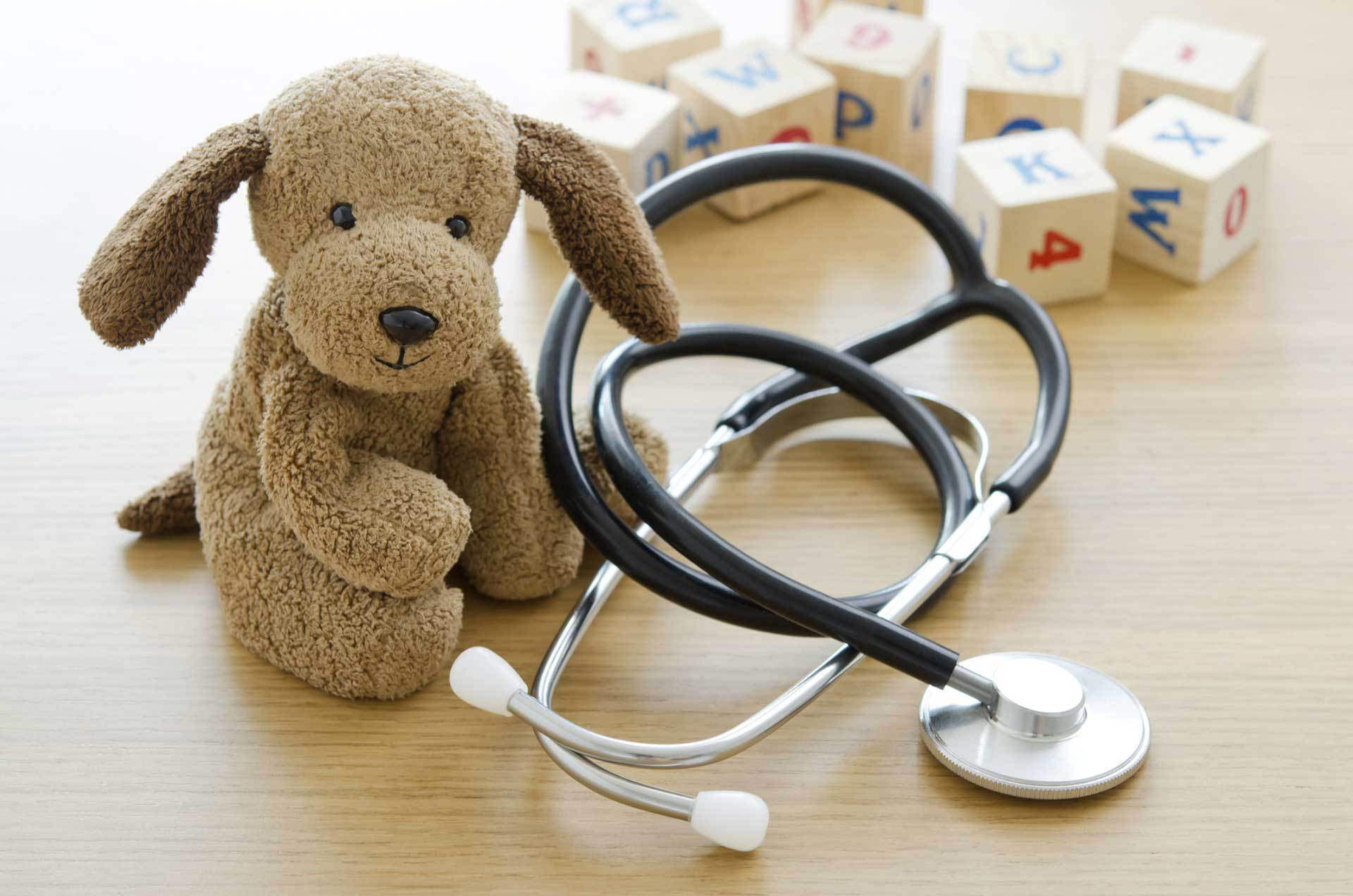 Stuffed teddy bear with stethoscope and blocks