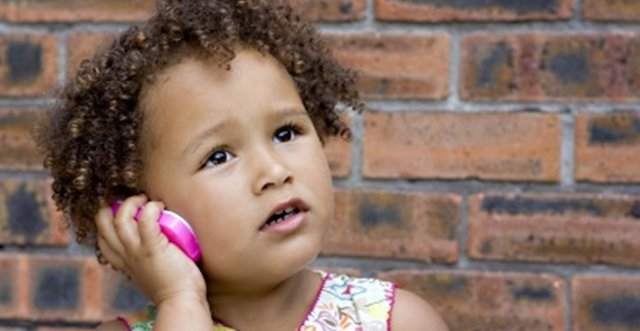 Young girl using toy cellphone