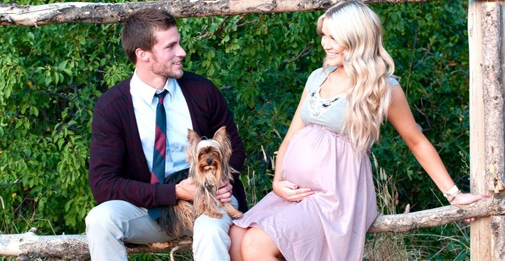 Pregnant couple sitting on tree branch